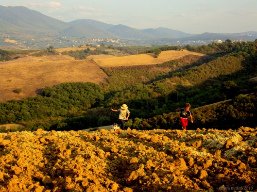 Boys running through plowed fields in Umbria, August 2012.